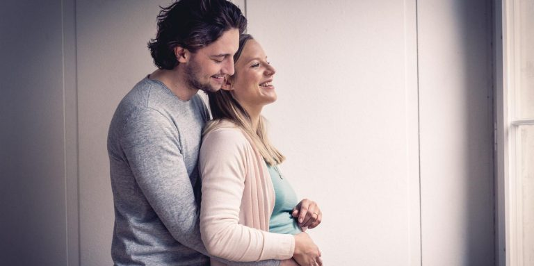 Man hugs pregnant woman
